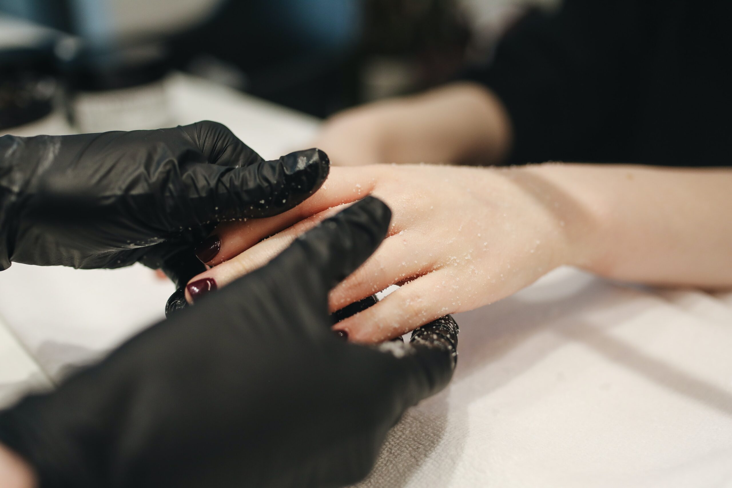 nail artists hands holding a womans hands to paint her nails