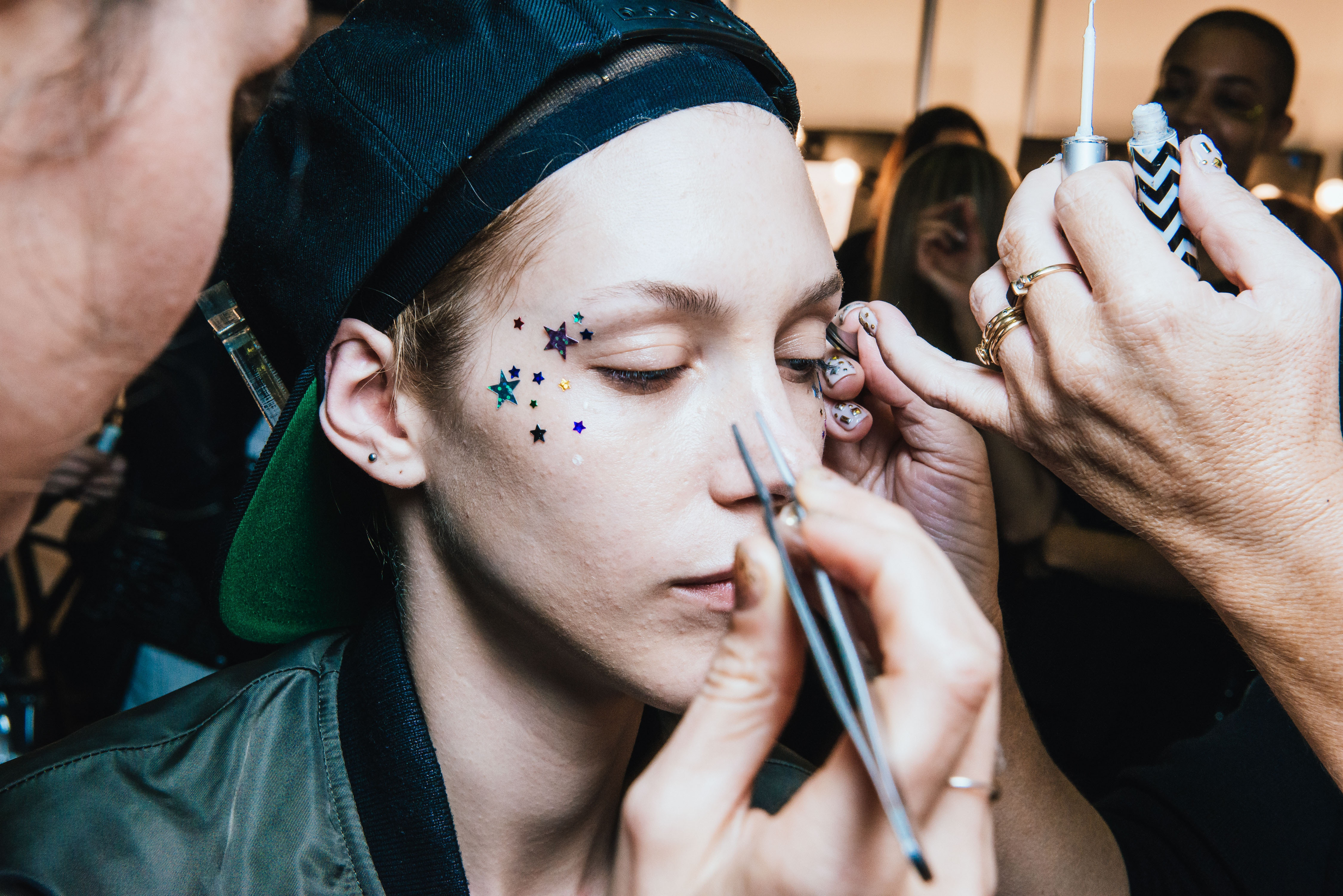 Makeup artists work on a model in a beauty convention