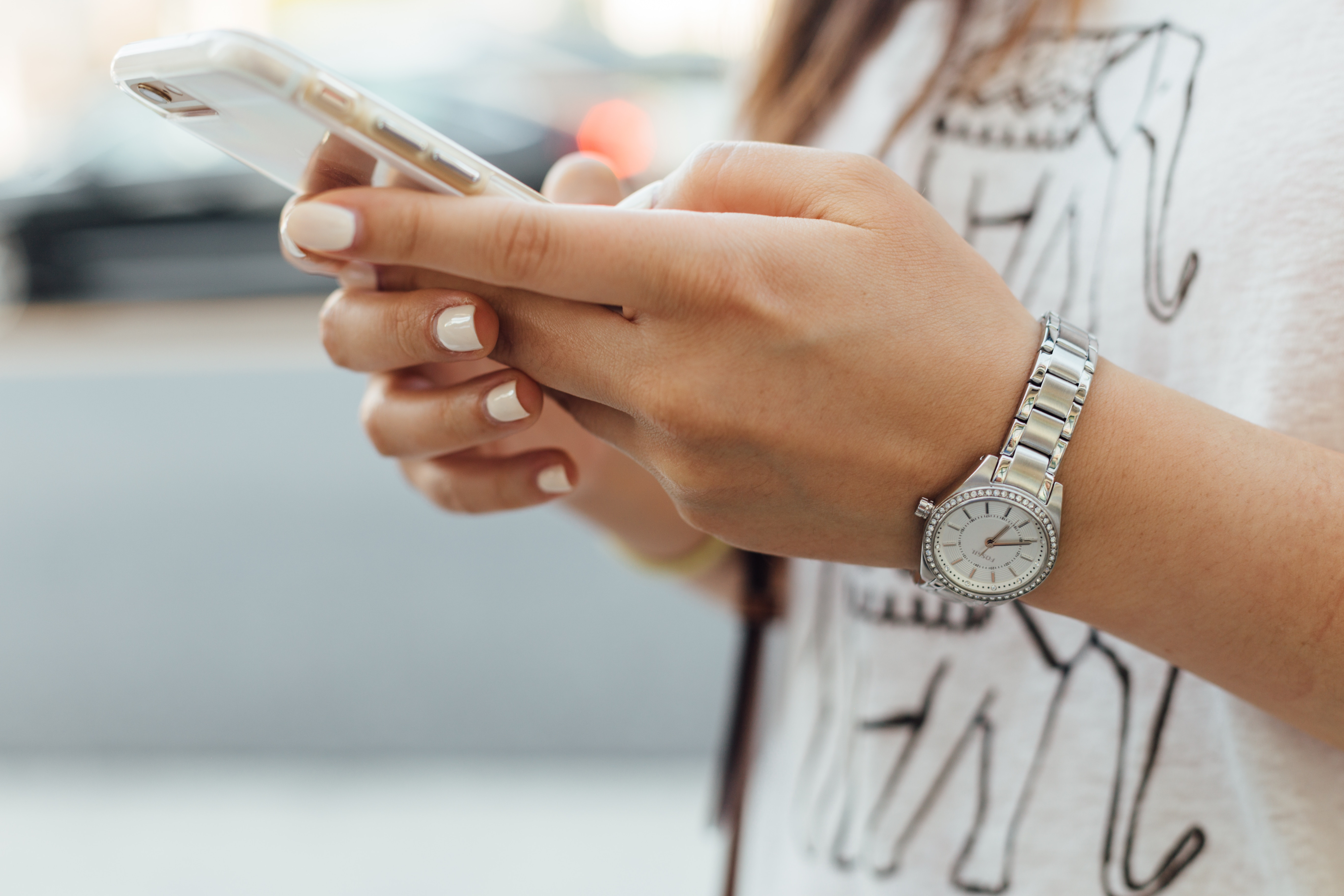 A woman with white nail polish holds a cell phone closeup shot