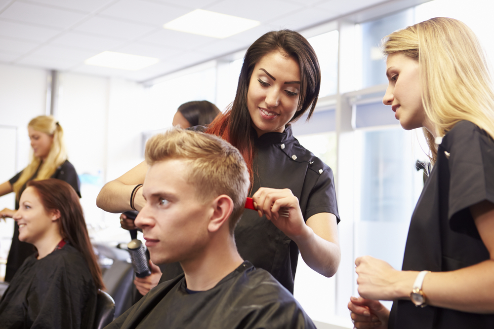 A cosmetology student cuts a man's hair under the supervision of an instructor