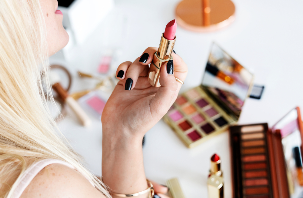 blonde girl holding lipstick with makeup on table