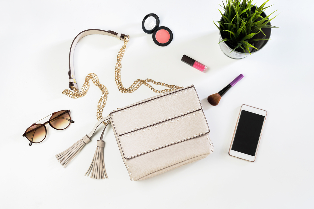 white purse flatlay with makeup and sunglasses