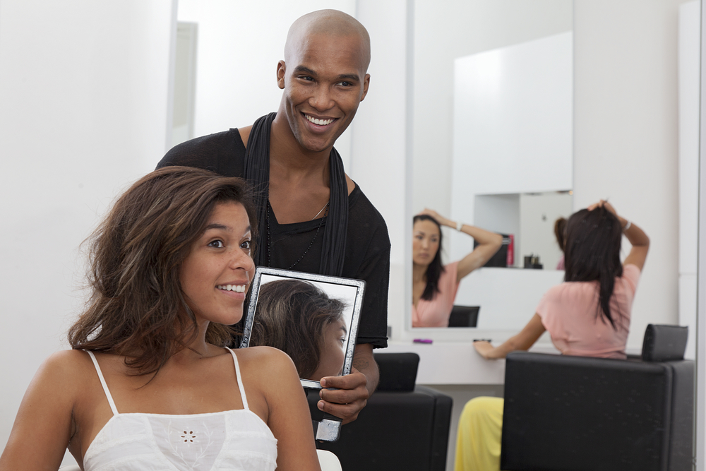 male hairstylist talking with female client about hair