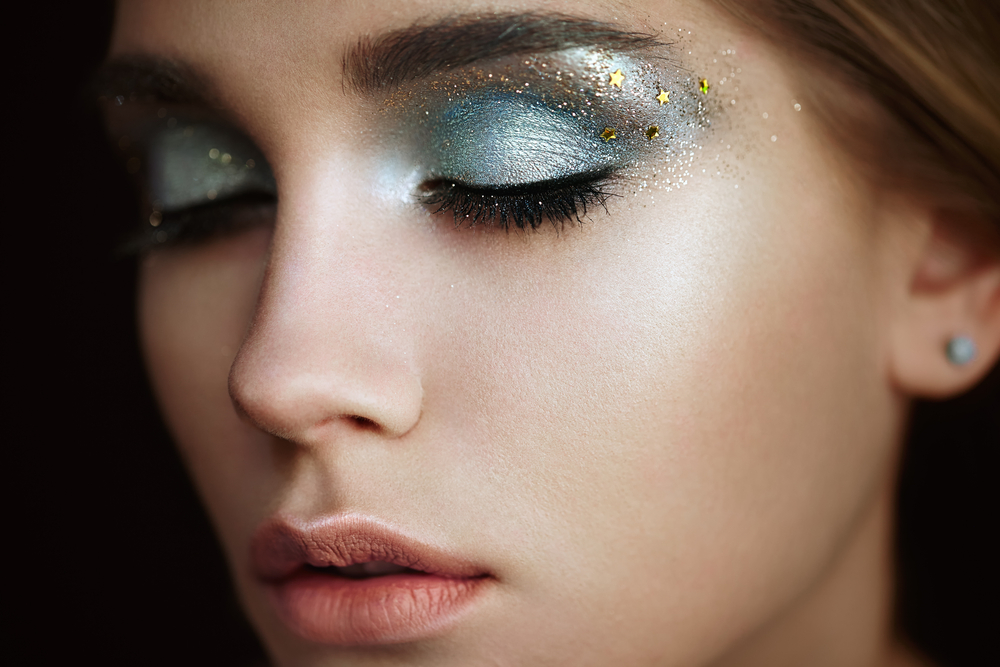 close up of slightly turned woman with blue and gold creative makeup
