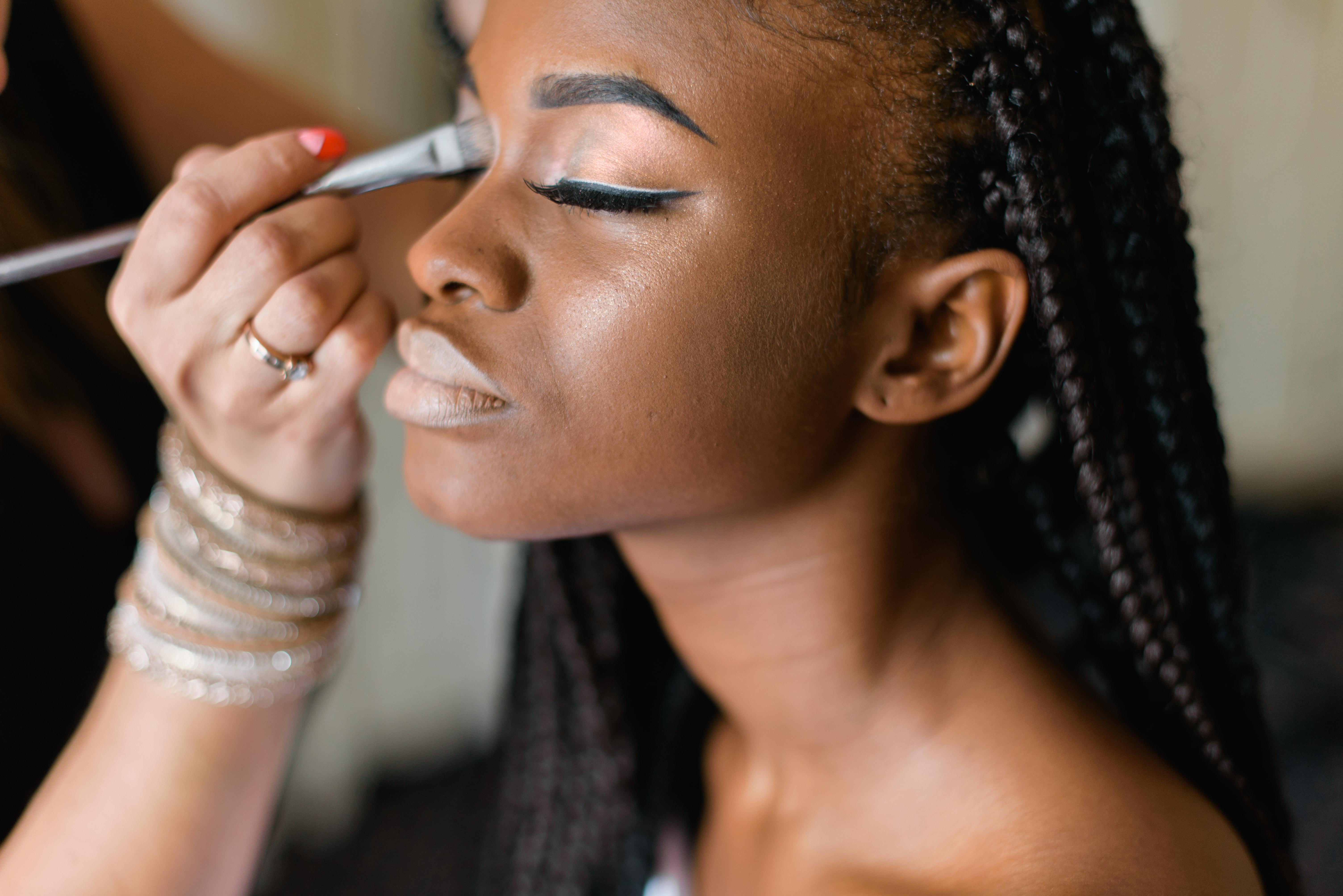 beautiful black woman with braids getting her makeup done