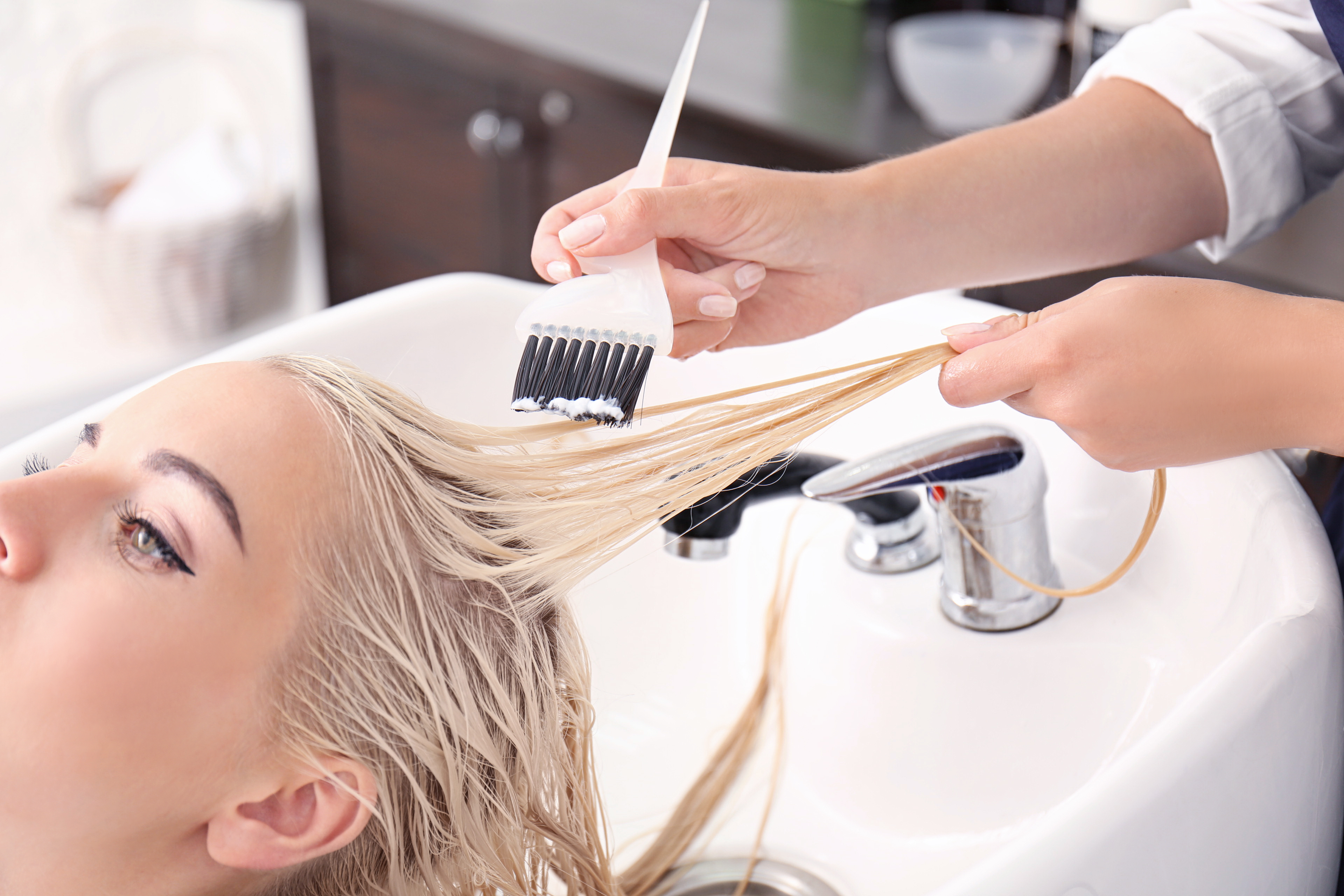 hands of a hairstylist putting color on platinum blonde client in sink