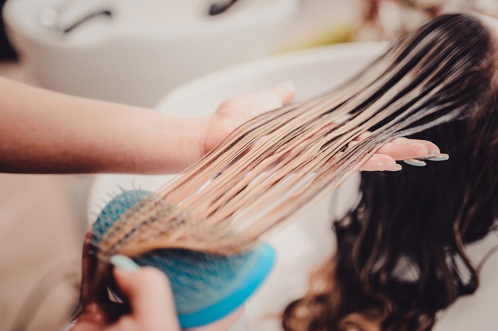 hairstylist brushing through wet balayage hair in sink