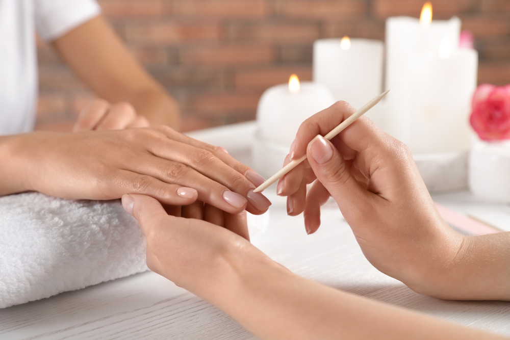 woman helping someone with manicure