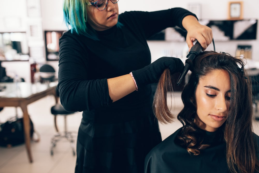 Hairstylist styling a woman's hair