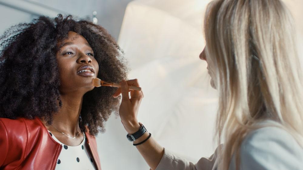Applying makeup at a fashion show.